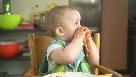 Funny child playing with spaghetti and sauce. Scene 6