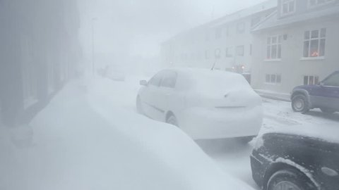 Whiteout blizzard and snowdrifts blocking sidewalk and cars in residential neighborhood during snow storm