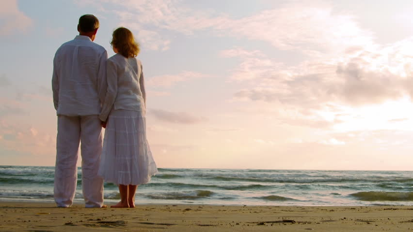 Older couple embrace on the beach while looking into the sunset.