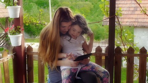 Mother and daughter using tablet in nature