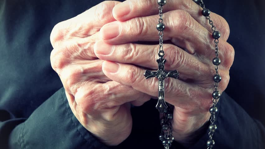Old lady hands holding a Catholic rosary or cucifix and praying to God in Heaven. Daily traditional Catholic devotional of an old lady or woman. | Shutterstock Video #8282308