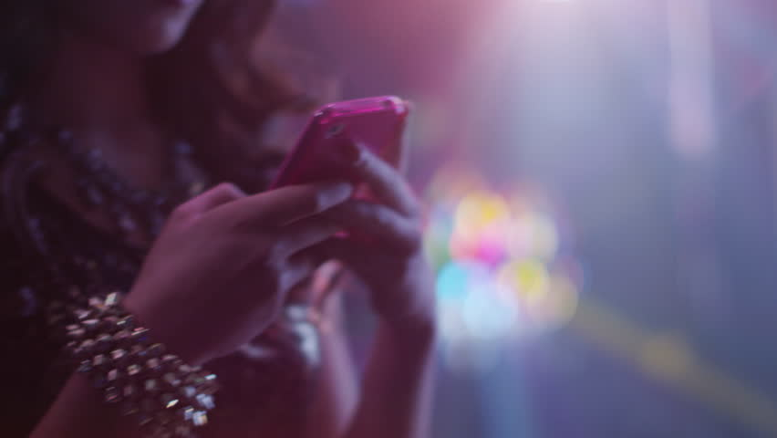Teen Girl is Typing Message on Phone in Nightclub.   Shot on RED Cinema Camera in 4K. Its easy scale, rotate and crop without loosing quality. ProRes codec  - Great for editing, color correction.