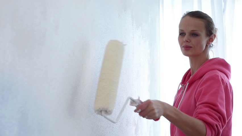 Home reconstruction: young woman painting a wall in her apartment, enjoying the work | Shutterstock HD Video #8392690