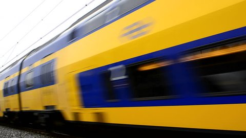 Dutch NS passenger train passing at an elevated railroad track at high speed.