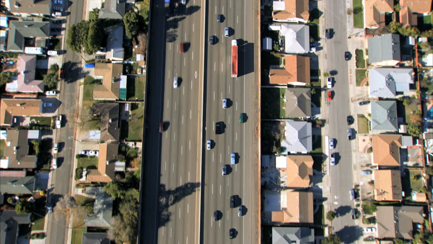 Aerial view following traffic on a freeway with suburban housing either side
