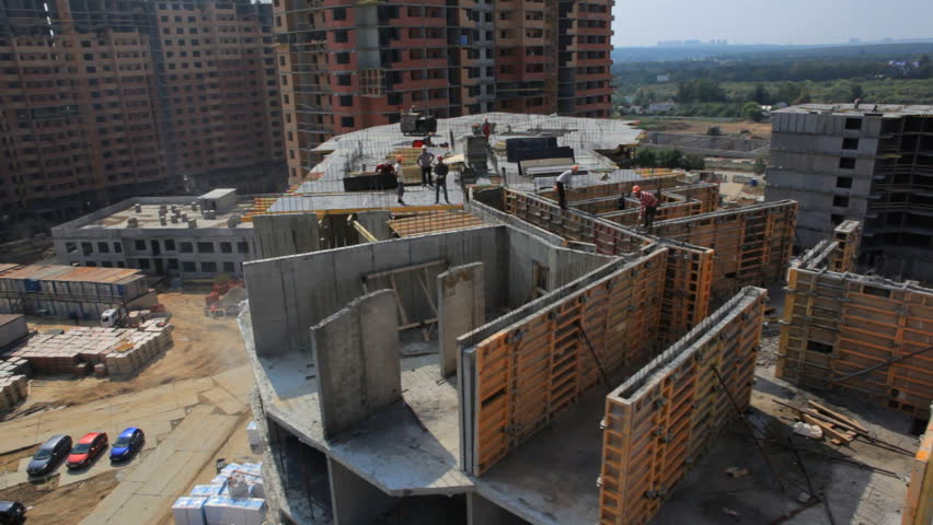 Construction industry. Aerial shooting.Camera flies over unfinished house. Builders are working on the roof #8456119
