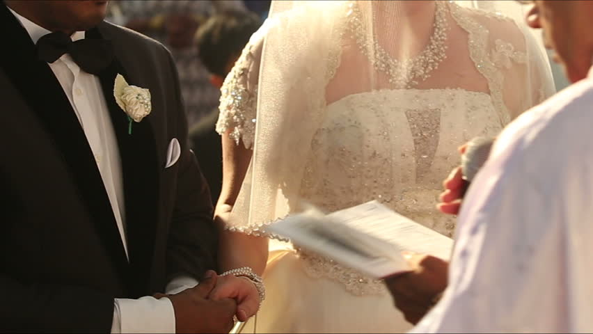 Catholic priest imposes a blessing for the bride and groom hands and speaks into the microphone