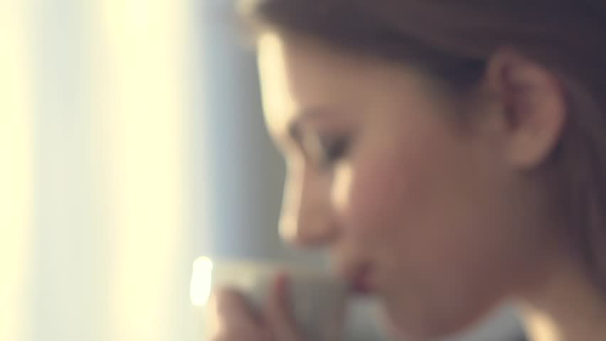Young beauty romantic woman drinking hot tea or coffee in morning light. Happy relaxed girl enjoying cup of warm steaming beverage. Slow motion, high speed camera 240 fps, HD 1080p
