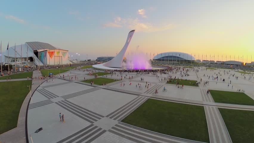 SOCHI - JUL 27, 2014: Crowd of people watch colorful fountain near sports stadiums at summer evening during sunset. Aerial view. Fountain was place for olympic fire during XXII Olympic games.
