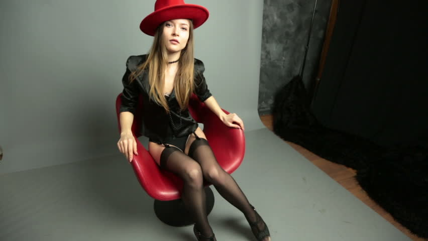 Young girl posing sitting in a red chair. Sexy in stockings.