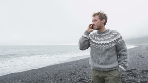 Smartphone man talking on smart phone walking on black sand beach on Iceland wearing Icelandic sweater by the ocean sea. Handsome Caucasian male model. 60 FPS.