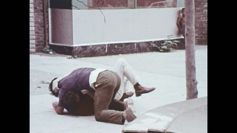 UNITED STATES 1970s: Police officers approach fighting men, pull men apart.