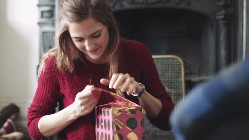 Young woman unwrapping gift