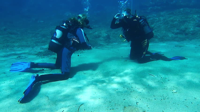 HALKIDIKI,GREECE- JULY 19 2014:Scuba diving instructor teaching her student to dive.Scuba diving is an adventure sport carried out in most countries of the world | Shutterstock HD Video #8697943