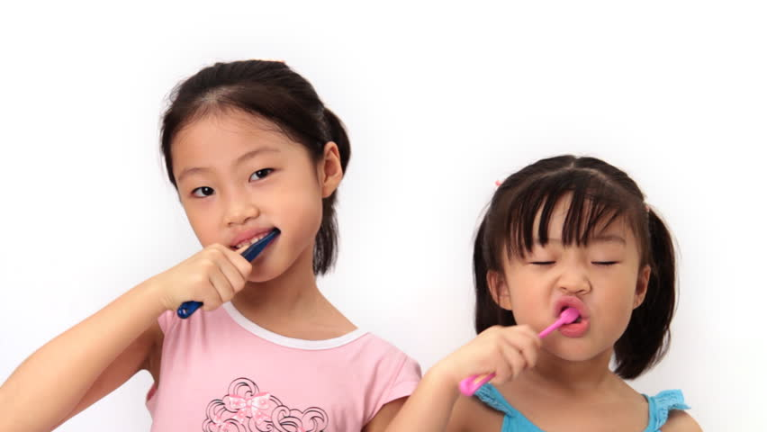 Two sisters look at camera and brush their teeth