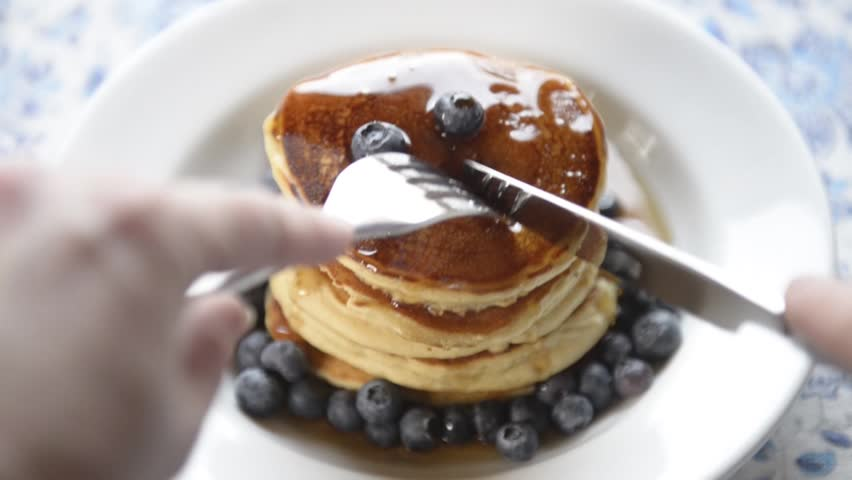 Woman eats delicious hot pancakes with fresh blueberries and natural maple syrup