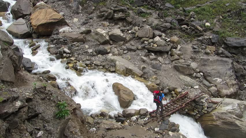 Hiker passing through a small wooden footbridge over a river in the Himalayas | Shutterstock HD Video #8719810
