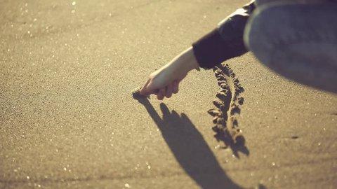 Teen girl drawing heart shape on the sand. Handheld shot