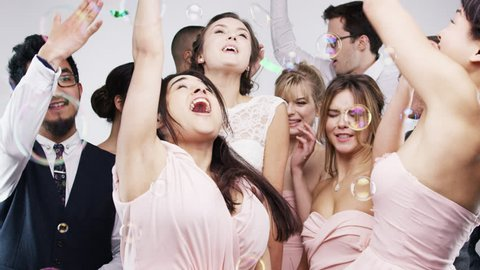 Multi ethnic group of friends dancing slow motion wedding photo booth series