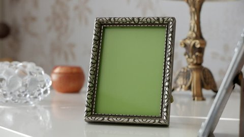 Single Picture Frame with Green Screen on side table. With decoration around. Tracking shot