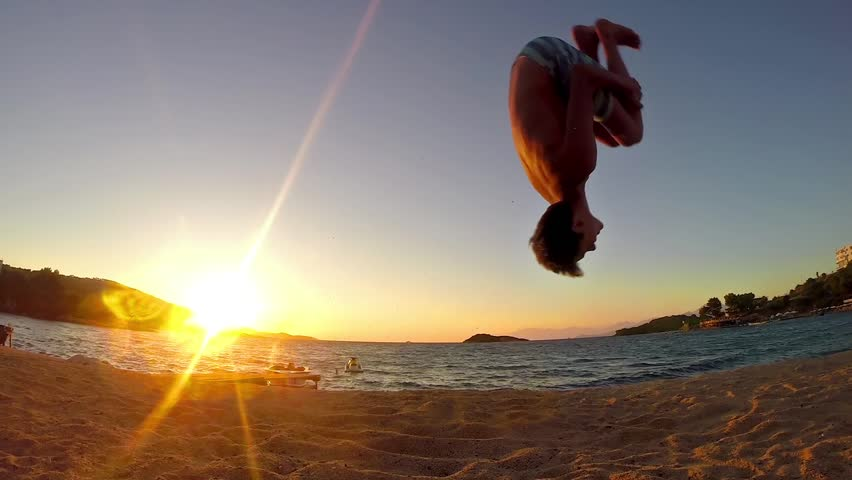85b7bc71a3719f teen doing gymnastics cartwheels and flip on the sunset beach in slow motion