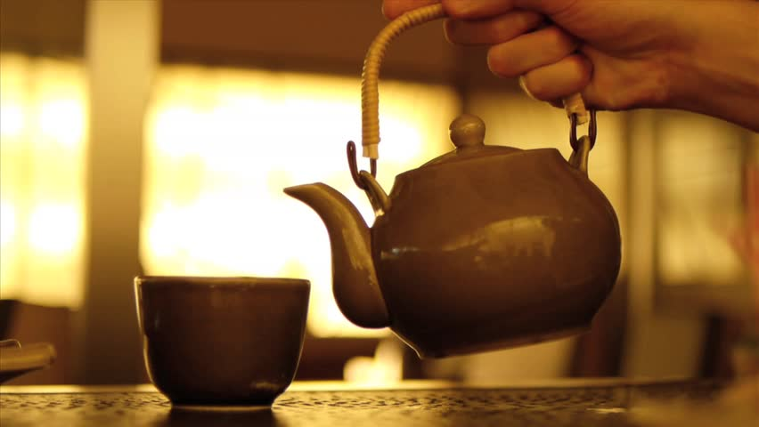 Hot water pouring from tea pot to tea cup