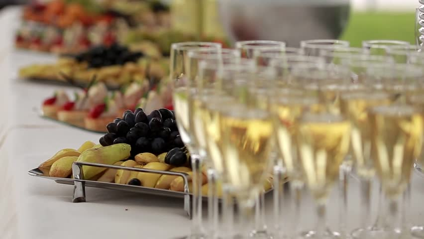Glasses of sparkling champagne and delicious snacks on a buffet table, dynamic change of focus