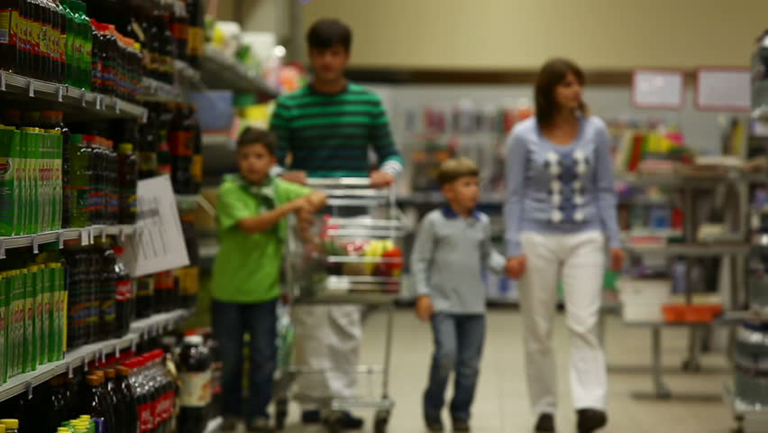 A family of four walking along the beverage row in the supermarket, the sons putting drinks into the trolley | Shutterstock HD Video #882883