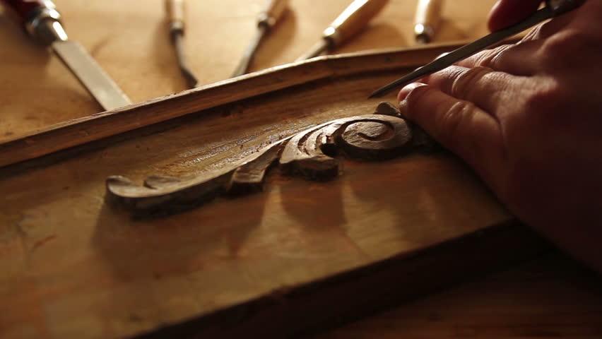 Close up of  carpenter restoring old furniture with chisel. dark color intensity.