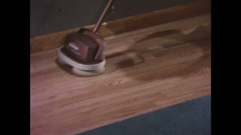 UNITED STATES 1960s: Floor polisher cleaning hardwood floor / Polisher cleaning baseboard / Polisher on linoleum floor / Polisher cleaning around chair leg.