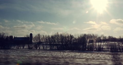 Driving through winter snow covered rural landscapes looking out the window.