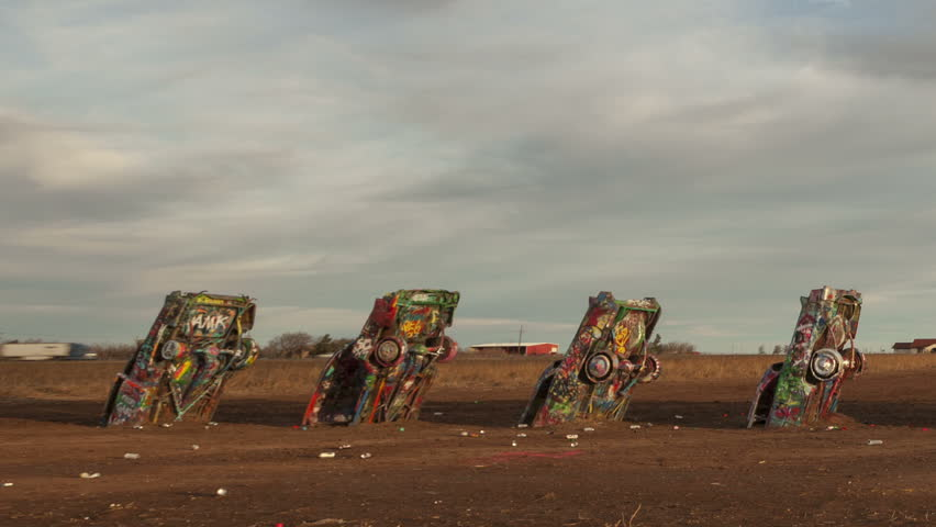 AMARILLO, TEXAS, USA - JAN 28. 2015: Time lapse close up pan shot of people spraying graffiti at Cadillac Ranch, a public art installation and sculpture in Texas, U.S. close to historic Route 66