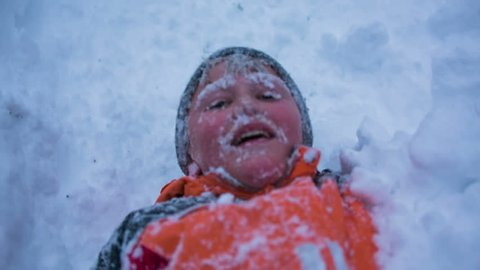 Boy descend the hill of snow under camera. Boy sliding down the snow directly in to camera with close up on funny white snowy cold face.