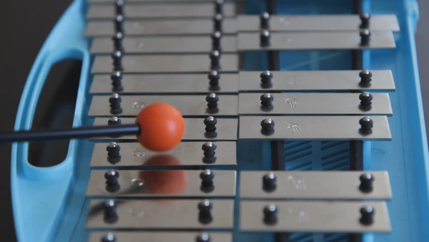 Glockenspiel. Playing a blue children's glockenspiel with an orange rubber mallet. Closeup and shallow DOF.