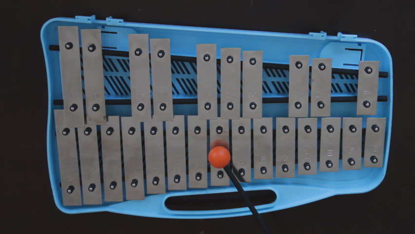 Glockenspiel. POV. Playing a blue children'?s glockenspiel with an orange rubber mallet.