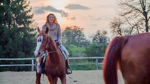 Woman on the horse with a sunset in the background. Slow motion RAW footage of a beautiful woman riding the horse on a ranch with beautiful sunset in the background.