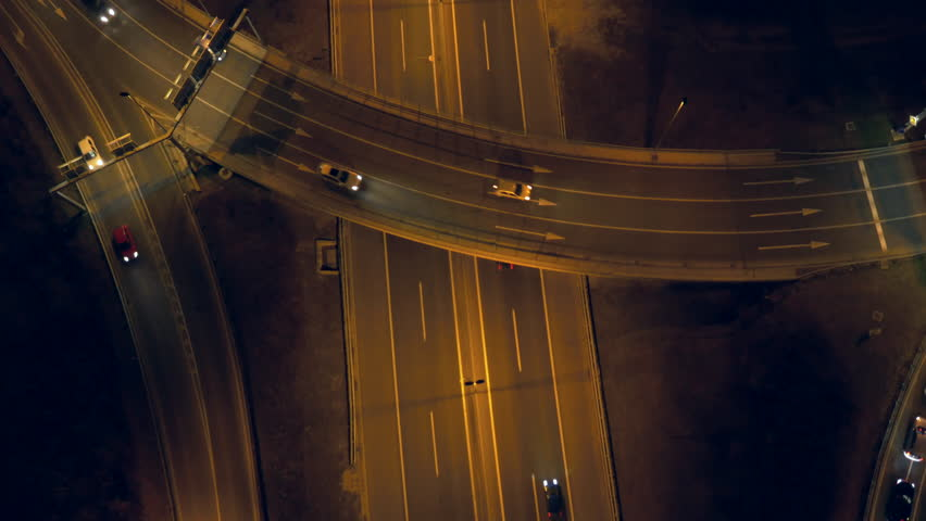 Aerial, vertical - Traffic at night. Roundabout over highway
