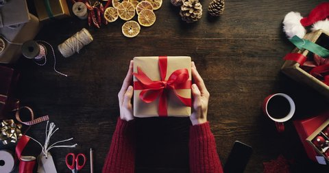 Top view hands holding christmas presents at wooden desk from above - Red Epic Dragon