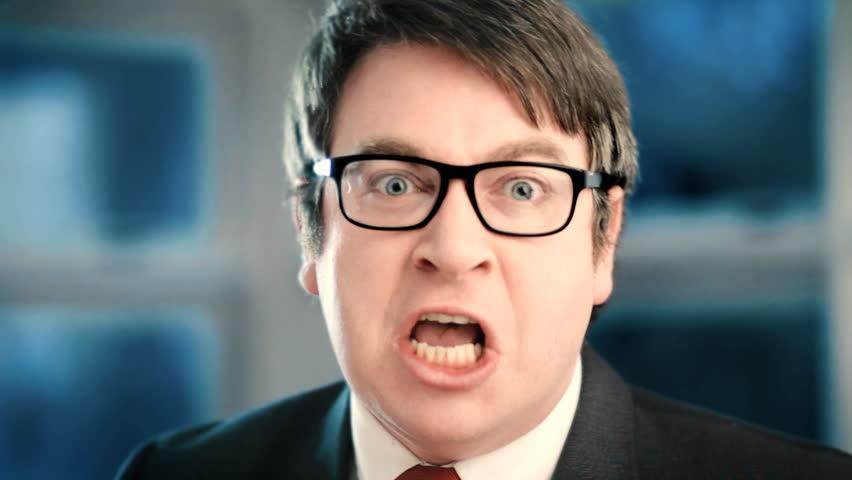 Angry businessman yelling at camera closeup