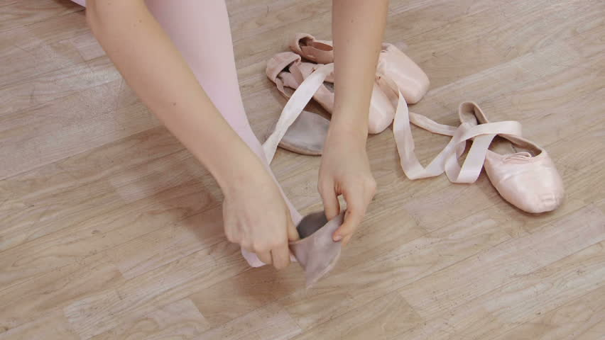 Girl putting on her ballet shoes..
