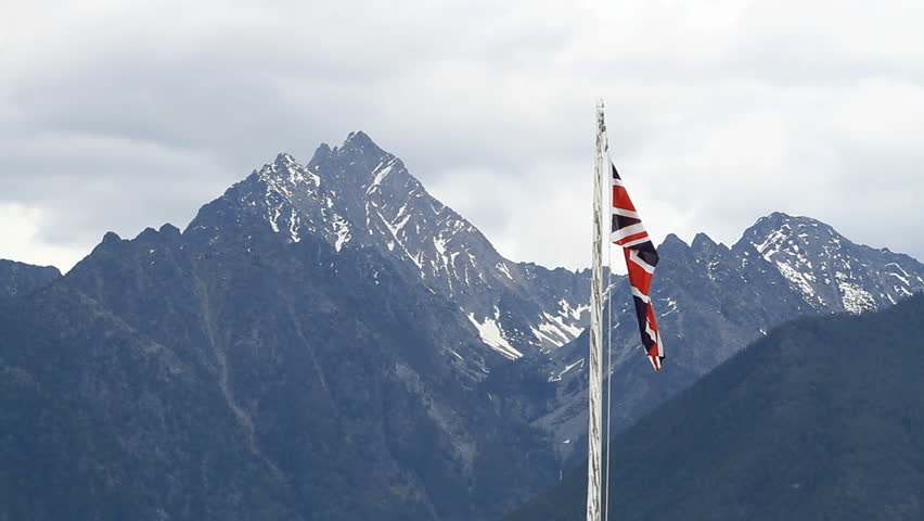 Canadian historic park flies the British Union jack flag on pole in historic Fort Steel, British Columbia, Canada. Banff National Park and glacial snow covered mountains in the distance.