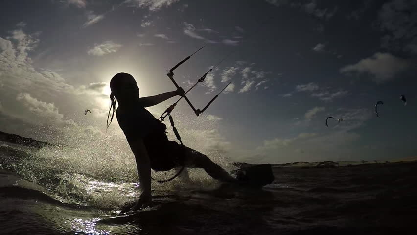 SLOW MOTION: Female kite-boarder riding and splashing water into camera