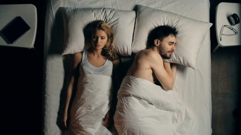 Above view of dissatisfied woman lying sleepless in bed and looking at her sleeping husband