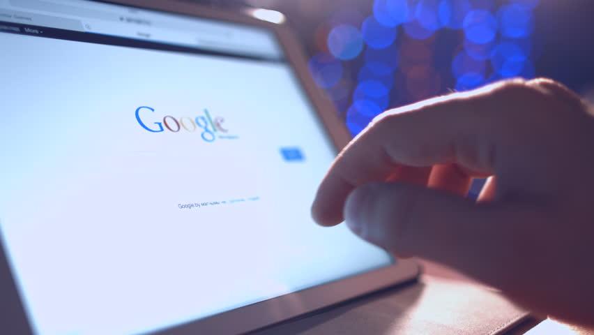 Minsk, Belarus - March 2, 2015: Man looking in google news on Tablet PC