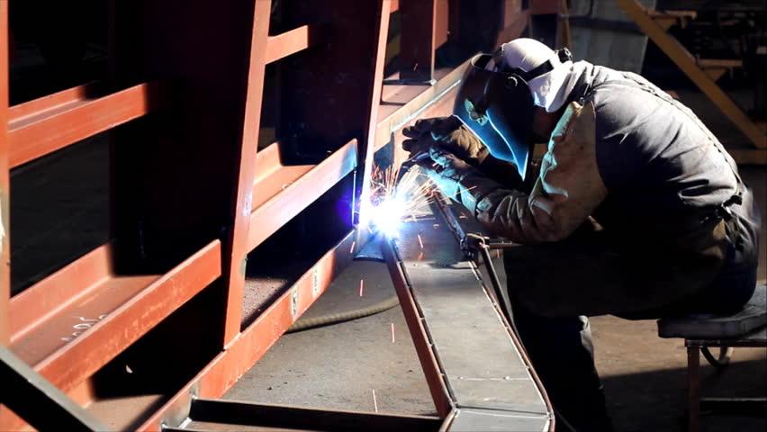 Welder at work in factory