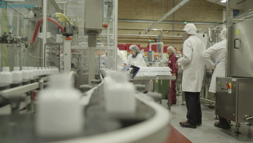 4K People at work. Pharmaceutical manufacturing facility factory. Pharma research and production science. Workers and technicians operate production machinery.  Drugs and cosmetics business industry.