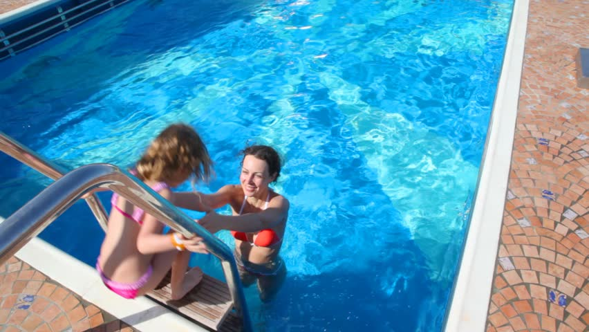 happy woman and little girl having fun in swimming pool on cruiser