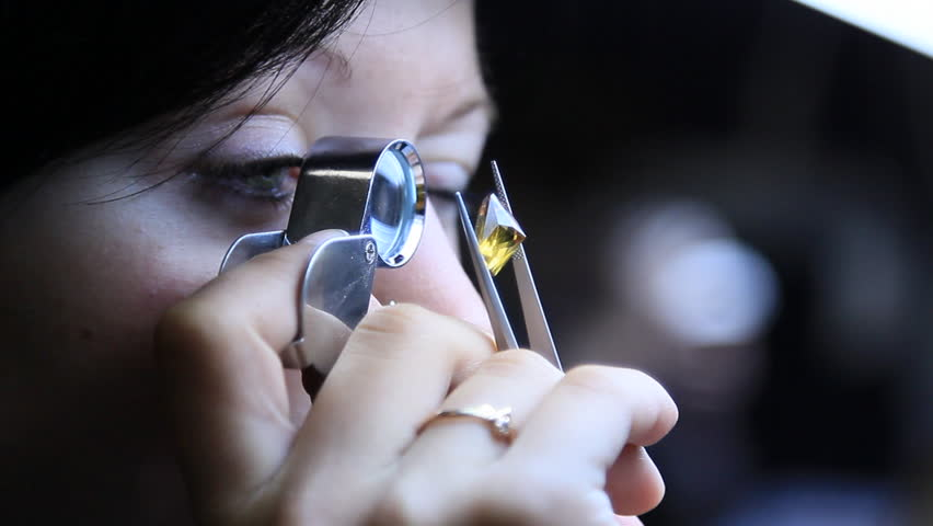Girl with a magnifying glass looks at a diamond to determine its purity.