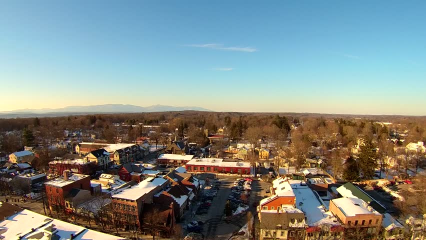 Rhinebeck, New York, aerial view of snowy roofs and center of cute town.. Aerials of small Hudson Valley towns in winter, with snow.