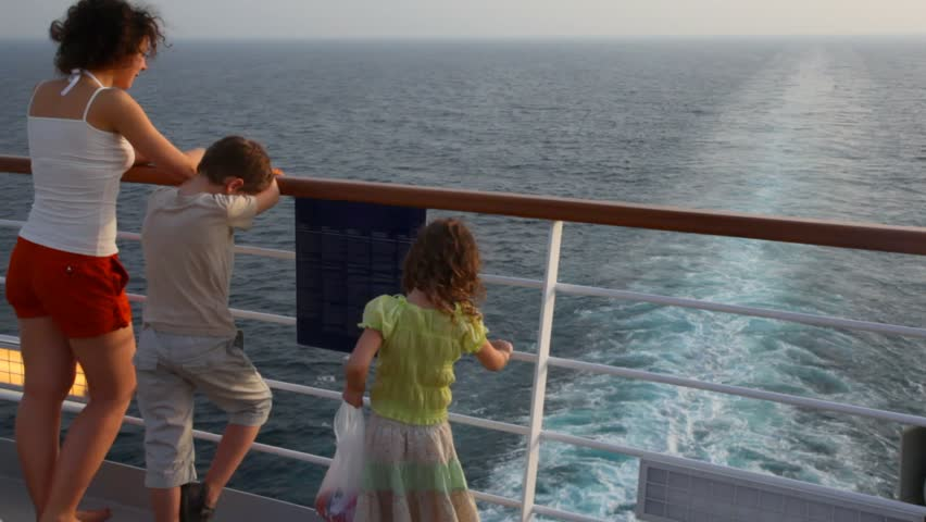 young mother with son and little daughter stand on deck of cruise ship
